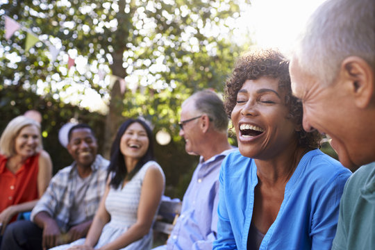 Group Of Mature Friends Socializing In Backyard Together