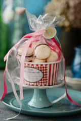 Macaroons gift wrapped in cellophane on cake stand