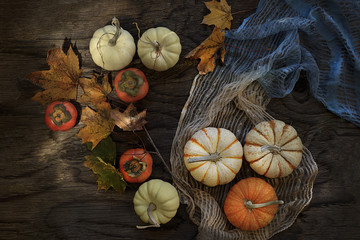 Overhead view of persimmons, pumpkins and autumn leaves on wooden table