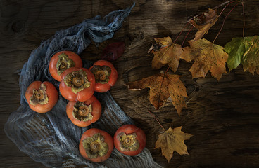 Overhead view of persimmons and autumn leaves on wooden table