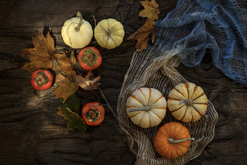 Overhead view of persimmons, autumn leaves and pumpkins on wooden table