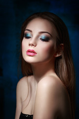 Beauty portrait of a beautiful girl with a bright evening make-up in blue.