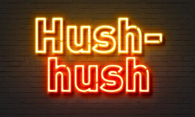 Hush-hush neon sign on brick wall background.