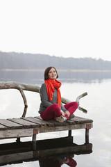 Germany, Berlin, Wandlitz, Mid adult woman sitting on pier, portrait