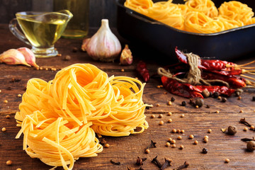 Raw spaghetti or pasta with sunflower oil, garlic, pepper and spice on black background, front view place for text