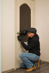 A man in a black jacket and dark glasses opens the door key