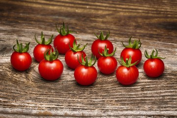 Wall Mural - Close-up of fresh, ripe cherry tomatoes on wood