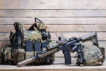 Rifle,flak jacket and helmet/Military bulletproof vest,assult rifle,helmet with night-vision device on wooden background