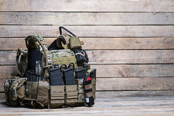 Army bulletproof vest/Military body armor,ammunition and ammo,radio and first aid tourniquet.On wooden table