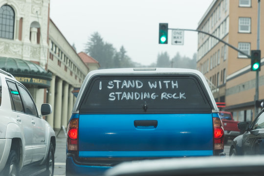 "Pickup truck with ""I Stand With Standing Rock"" on back window"