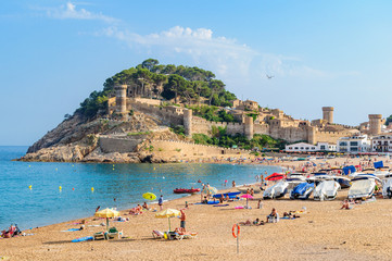 A view of the ancient fortress of Tossa de Mar, in the foreground beach.