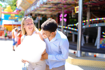 Newlyweds strolling in luna park, looking at each other, cuddlin