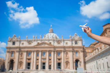 Closeup toy airplane on St. Peter's Basilica church in Vatican city background. Concept of travel imagination.