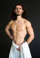 photo muscular half naked guy with curly hair in a white drapery standing