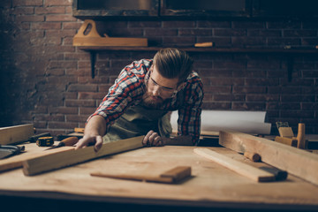 Bearded handsome cabinetmaker at the tabletop with tools.  Stylish craftsman with brutal hairstyle and saved glasses holding woodenplank at his workstation