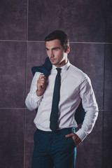 Portrait of young successful handsome businessman holding jacket