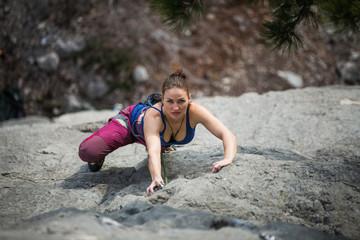 woman climbs a rock