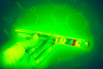 Word toxic in test-tube holding a gloved hand