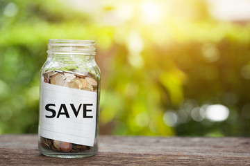 SAVE word with coin in glass jar with. Savings and financial investment concept.