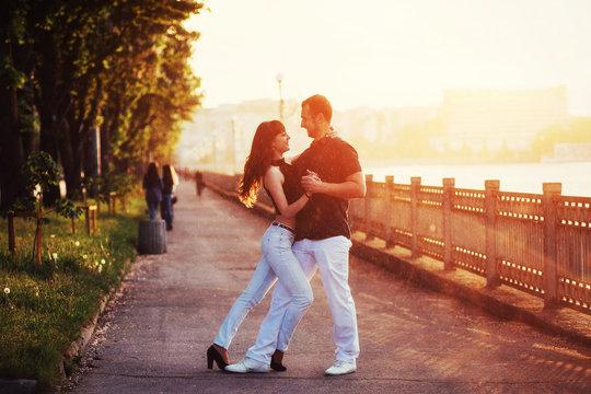 young couple dancing tango on the embankment
