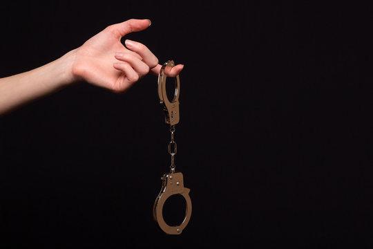 Female hand holding handcuffs on a dark background