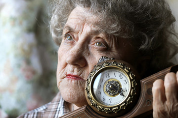 Thoughtful grandmother with clock