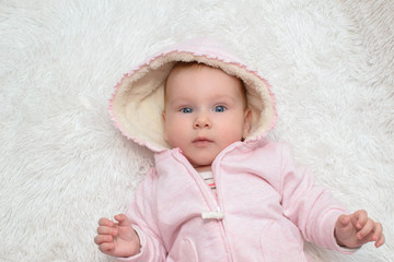 Cute beautiful baby in pink suit with a hood on her head lying smiling on the white carpet