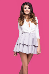 Young pretty girl in a short skirt is standing on a pink background