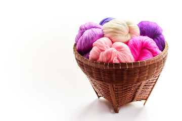 Group of pure colorful cotton in rattan basket on white isolated background.