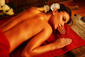Massage of woman in spa salon. Girl on candles background in massage and skincare spa salon. Luxary interior in oriental therapy salon. Portrait of female bare back with smooth skin have relax .