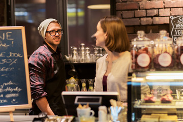 happy bartenders at cafe or coffee shop counter