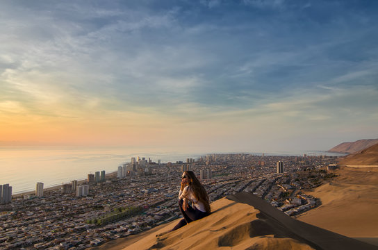 Young woman sitting at the sand dune and overlooking desert, city and ocean