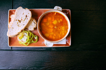 Goulash red soup with bread on wooden background
