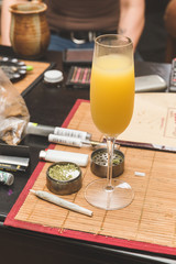 Mimosa next to joint, grinder, lighter, and other cannabis accessories