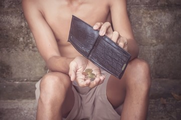 Man sitting in front of old brickwall and holding a empty wallet