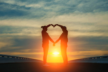 silhouette of couple in love.Focus on hands at sunset.