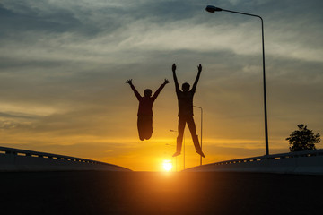 silhouette couples Jumping at sunset