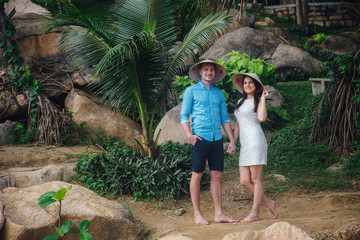 couple in love hugging in beautiful place with palm trees in summer. man wear the blue shirt and the girl in a white dress with vietnamese hats on their heds. Concept of honeymoon