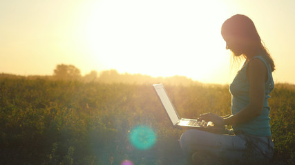 Young pretty woman typing on a laptop outdoors at beautiful sunset sitting on the grass with amazing lense flare effects