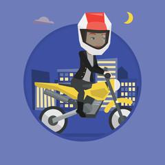 Woman riding motorcycle at night.