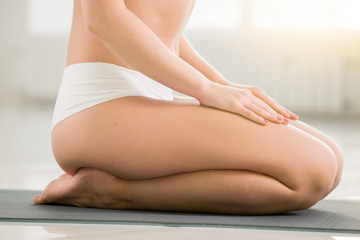 Young woman practicing yoga, sitting in vajrasana exercise, seiza pose, working out, wearing sportswear, shorts, indoor, white color room background, close up of legs