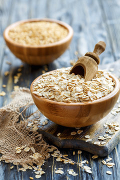 Bowl with oat flakes and wooden scoop.