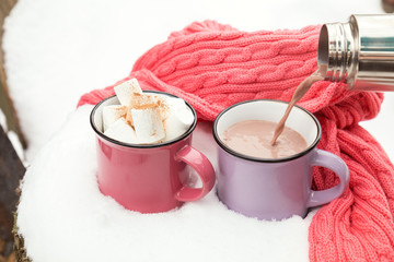 Pouring hot chocolate in the cup. Hot chocolate with marshmallow in pink and violet two cups wrapped in a cozy winter pink scarf on the snow-covered table in the garden. Coloring and processing photo