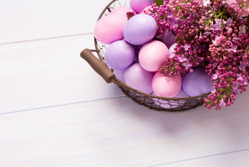 Easter eggs and  lilac  flowers on  pink wooden table. View from above.