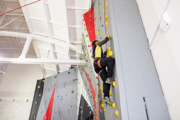 man climbing on practical wall indoor, with belay carabiners and rope