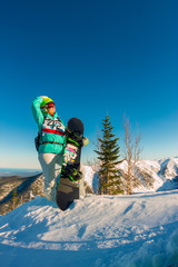 Woman with snowboard freerider on the mountain sunrise