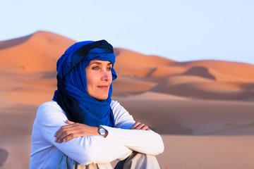portrait de femme avec un chèche assise dans le désert
