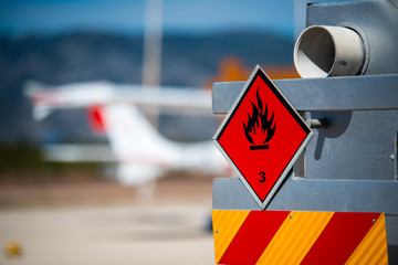 Rear view of service and refuelling truck on an airport with an aircraft in the blurry background. Chemical hazard, flammable liquids. Wall mural