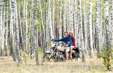 Happy couple on a motorcycle in a birch grove.