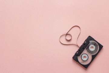 Audio cassette tape in the shape of heart on pink background.